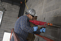 Francisco Gonzalez (from center left) and Biem Lome drill a hole for a gas line that will be used to heat up a kitchen, stove and water heater, Thursday, January 30, 2020 at the new Springdale Fire Department #8 in Springdale. Check out nwaonline.com/200131Daily/ for todayÕs photo gallery.<br /> (NWA Democrat-Gazette/Charlie Kaijo)<br /> <br /> The city has dedicated all of the money in the 2018 fire department bond. The bond budget included three new fire stations and an expansion of the departmentÕs training center.
