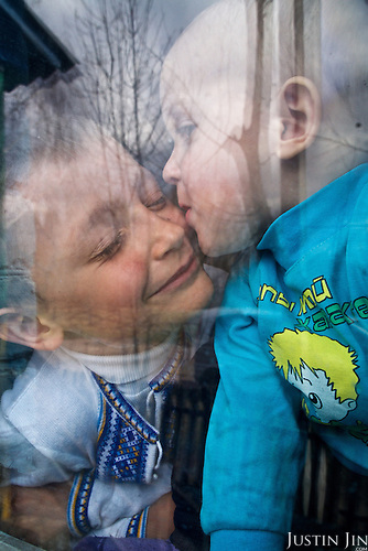 Bogdan, 7, is kissed by his brother Kirill, 2, at home in Nevhody Village in Ukraine. <br /> <br /> The village is built to house those affected by the nuclear disaster in the Chernobyl power station disaster happened on 26 April 1986. <br /> <br /> The children suffer from multiple health problems linked to radiation exposure. <br /> <br /> 30 years on, the area is still too heavily contaminated for human activity.