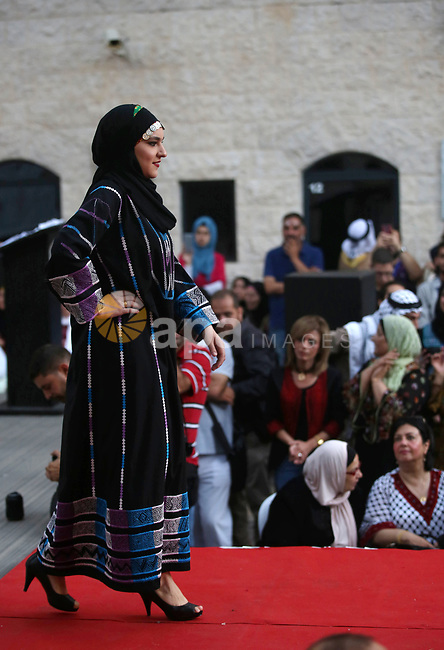 A Palestinian woman wearing traditional dress creation takes part during a fashion show marking Traditional Palestinian Dress Day, in the West Bank city of Nablus on August 22, 2017. Photo by Ayman Ameen