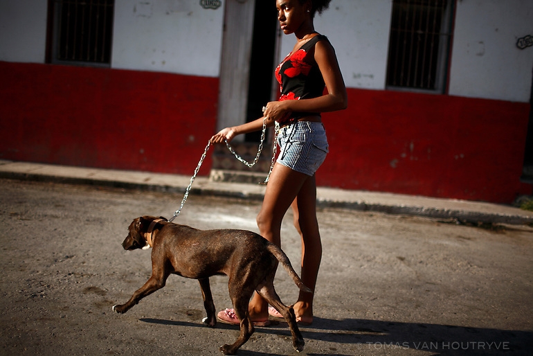 A woman walks a dog through an alley in Havana, Cuba on 10 October 2008.