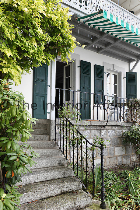 Climbing plants amble up the the iron railings towards the entrance of the chalet, with its green and white awnings and fretwork balconies