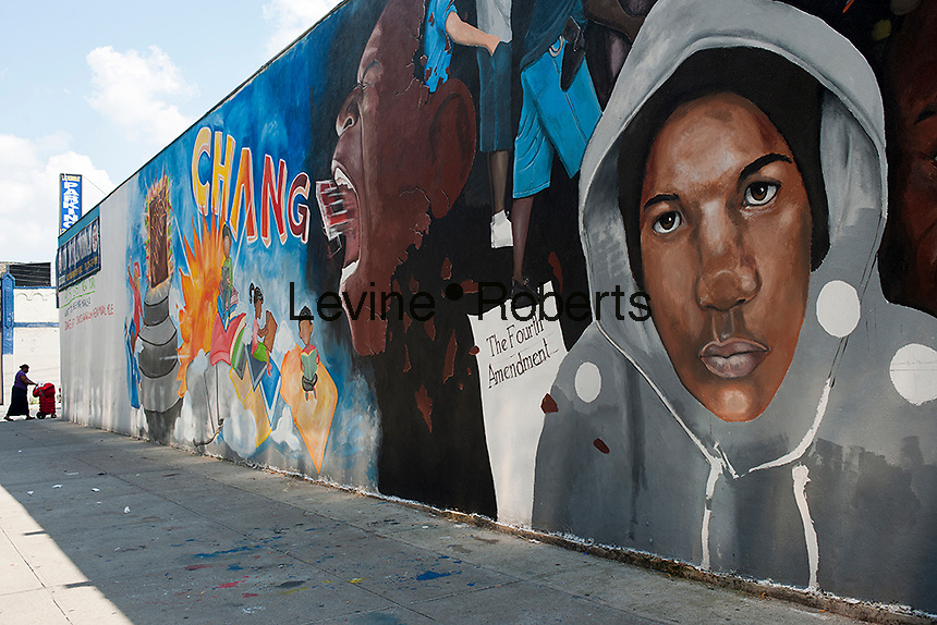 An unfinished mural in the East New York neighborhood of Brooklyn in New York on Saturday, September 1, 2012 commemorates Trayvon Martin and protests the NYPD policy of stop and frisk.  The artists feel the policy singles out people of color and creates an atmosphere of fear and a de facto martial law in neighborhoods where it is enforced. MMartin was shot and killed by neighborhood watch volunteer George Zimmerman in February. The shooting has raised the consciousness of the public about racial profiling and the suspiciousness of young black men based on their clothing.  (© Richard B. Levine)