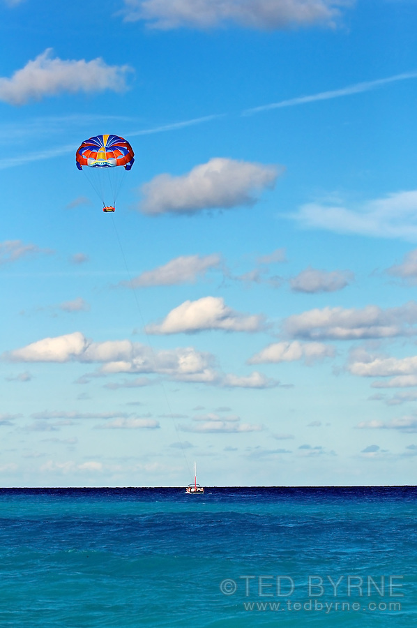 Parasail being towed high over a boat over a turquoise ocean