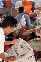 Former hostages from Thailand and Myanmar (Burma) await processing and return to their home countries, after being freed by the Indian Navy. Held by Somali pirates for 10 months the hostages were relaxing in a temple outside a local police station following their ordeal, some reading local newspapers with their story.