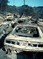 burned automobiles along neighborhood street in Oakland Hills fire of October 1991. burn, burned, fire, hot, insurance, loss, damage, arson, charred, ruins, disaster. Oakland California USA Oakland Fire Oct. '91.