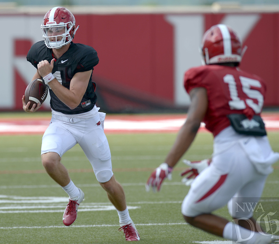NWA Democrat-Gazette/ANDY SHUPE<br /> Arkansas quarterback Daulton Hyatt (left) rolls outside of the pocket as defensive back LaDarrius Bishop (15) pursues Thursday, Aug. 9, 2018, during practice at the university's practice facility in Fayetteville. Visit nwadg.com/photos to see more photos from practice.