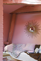 A sofa is situated beneath a sunburst convex miror in this pink attic bedroom