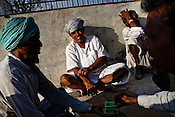 Local villagers gather to play cards at the village centre in Ramdevra village  in Churu district of Rajasthan, India. The National Rural Employment Guarantee Act (NREGA) that has created a source of additional income for families living below the poverty line by providing a minimum 100 days of employment assured under the Act. Photo by Sanjit Das