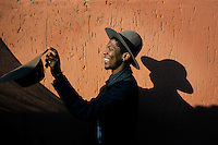 SOWETO, SOUTH AFRICA JULY 3: Floyd Avenue a young designer part of the group Smarteez design collective plays with one of his hats outside his family home on July 3, 2014 in Jabulani section of Soweto, South Africa. Soweto today is a mix of old housing and newly constructed townhouses. A new hungry black middle-class is growing steadily. Many residents work in Johannesburg but the last years many shopping malls have been built, and people are starting to spend their money in Soweto. (Photo by: Per-Anders Pettersson)