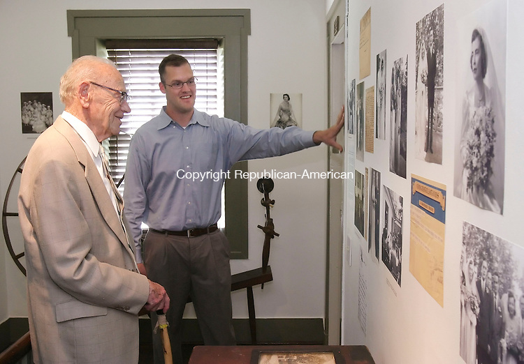 WASHINGTON, CT 06/01/08- 060108BZ11- Robert DeCourcy, of Washington, and his grandson, Sean DeCourcy, of Sacramento, CA, look at dozens of photographs, including pictures of the elder DeCourcy's wedding, on the walls of the Gunn Museum during a wedding dress exhibition.  <br />  Jamison C. Bazinet Republican-American
