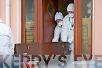 Members of Crime Scene Investigation Unit carry the bodies out of the house they were murdered in in Killorglin