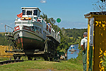 Lockmaster overseeing tourist boat on cable-cradle approaching uphill basin: Overland transportation of boats on rail cars at the Elblag Canal (Polish: Kanal Elblaskie, German: Oberlaendischer Kanal), Masuria, Poland, Europe. No releases available. ---Info: A system of rail-mounted cable trolleys on skipways and traditional locks are connecting the various sections of the Elblag Canal. A 100 metre difference in water levels is overcome during a length of 80 km between Ostroda and Elblag. The rail lift devices are mechanically driven by water power.--- HISTORY: The canal was designed in 1825-1844 by Georg Steenke, carrying out the commission given by the king of Prussia. Construction began in 1844. As the route was not important enough to justify building expensive, traditional locks between lakes, an ingenious system of tracks was employed instead, though the canal includes a few locks as well. Built originally under the name Oberländischer Kanal (Overland Canal) and situated in the Kingdom of Prussia, it was opened in 1860. Since 1945 the canal has been located in Poland. After wartime damage was repaired, it was restored to operation in 1948. Today it is used mainly for recreational purposes. It is considered one of the most significant monuments related to the history of technology on the territory of modern Poland..