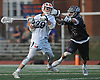Aidan Mulholland #29 of Manhasset, left, recoils for a shot that resulted in a goal in the first quarter of the 131st Woodstick Classic against Garden City at Manhasset High School on Saturday, April 29, 2017. Manhasset won by a score of 10-8.