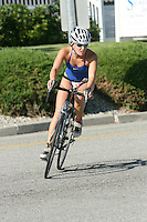A woman triathlete finishing her bike session at the ChelanMan Multi-Sport Weekend in Chelan