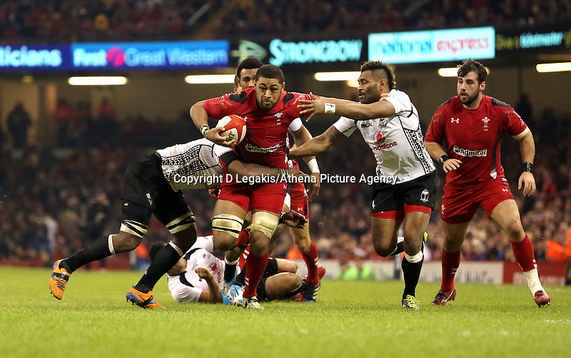Pictured: Taulupe Faletau of Wales (with ball) is brought down by Josh Matavesi (L) and Nikola Matawalu (2nd R) of Fiji. Saturday 15 November 2014<br />