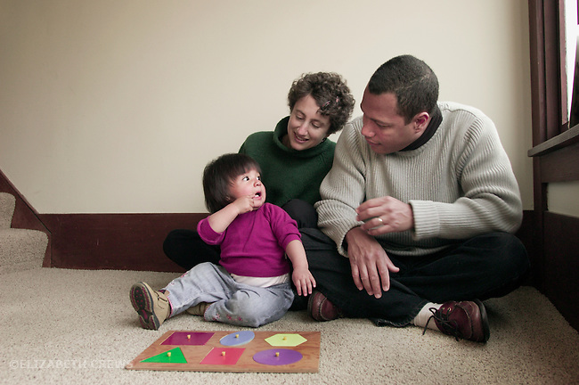 Berkeley CA Adoptive parents, father Cuban, encouraging Guatemalan daughter in doing geometric form board puzzle MR
