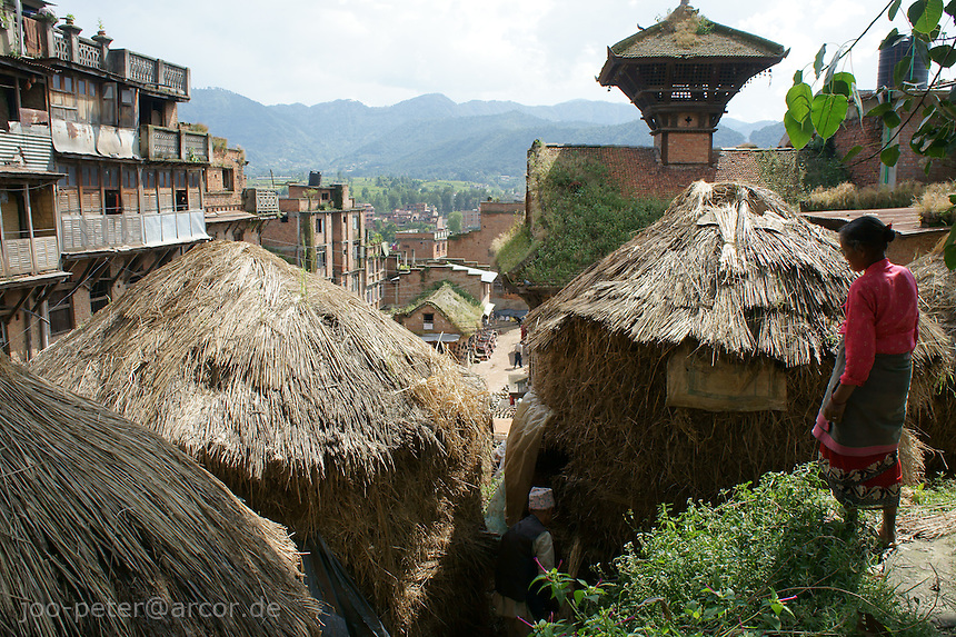 Old man picks dry straw for fire out of a traditional storage pile, watched by his wife, close to pottery Square in Bhaktapur, Nepal. In the background mountains, showing typical landscape of mountains surrounding  Kathmandu valley