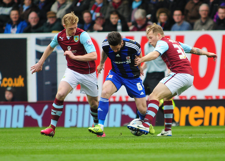 Middlesbrough's Jacob Butterfield shields the ball from Burnley's Ben Mee, left, and Burnley's Scott Arfield <br /> <br /> Photo by Chris Vaughan/CameraSport<br /> <br /> Football - The Football League Sky Bet Championship - Burnley v Middlesbrough - Saturday 12th April 2014 - Turf Moor - Burnley<br /> <br /> &copy; CameraSport - 43 Linden Ave. Countesthorpe. Leicester. England. LE8 5PG - Tel: +44 (0) 116 277 4147 - admin@camerasport.com - www.camerasport.com