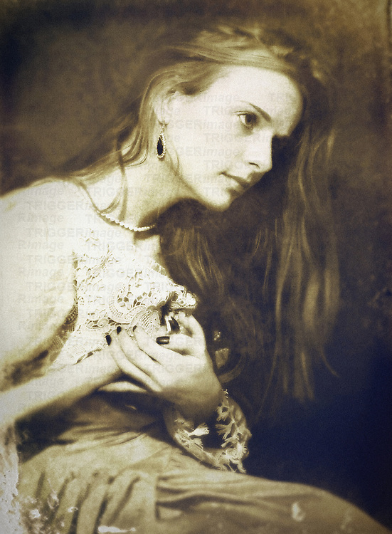 A woman , seated, in a vintage outfit and long hair, with painful expression and hands raised to her chest.