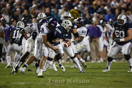 BYU's QB Max Hall (15)  is sacked by TCU's D.J. Yendrey (55, front) and TCU's Wayne Daniels (96). BYU vs. TCU college football Saturday, October 24 2009 in Provo.