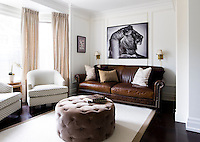 The leather sofa and tub chairs provide a comfortable sitting area in an ante-room, where the neutral tones give the room a relaxing ambiance.