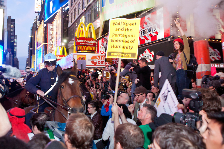 """Police officers threaten protesters with """"Occupy Wall Street"""" by advancing on horseback in Times Square on October 15, 2011 in New York City.  While crowd estimates numbered in the tens of thousands, police tactics (including nets, motor scooters, barricades, arrests, and intimidation by riders on horseback) prevented the crowd, which had been split up, from joining together as one in the middle of Times Square."""