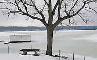 Snow covers picnic tables along a frozen lake in winter.