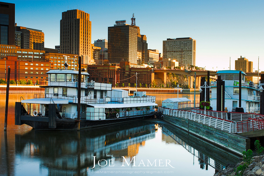 View of St. Paul, Minnesota skyline and the former tugboat, now the Covington Inn Bed and Breakfast at dawn from the shore of Mississippi River.