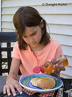 1B15-510z  Child eating breakfast of pancakes with honey, PRA