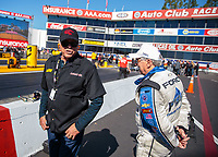 Feb 8, 2019; Pomona, CA, USA; NHRA funny car driver John Force (right) talks with Don Prudhomme during qualifying for the Winternationals at Auto Club Raceway at Pomona. Mandatory Credit: Mark J. Rebilas-USA TODAY Sports