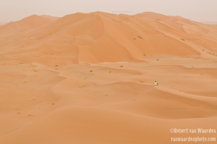 A man alone on the sand dunes of the Empty Quarter, Ar Rub Al Khali, Oman.