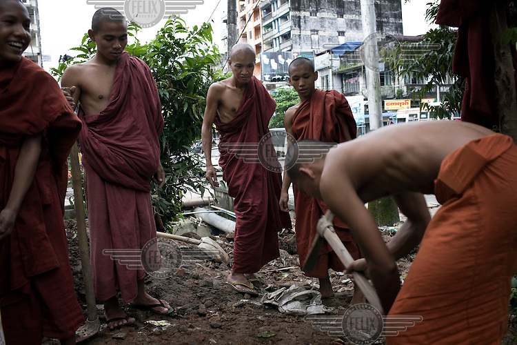 A group of monks make repairs to their monastery in central Rangoon after heavy rains.