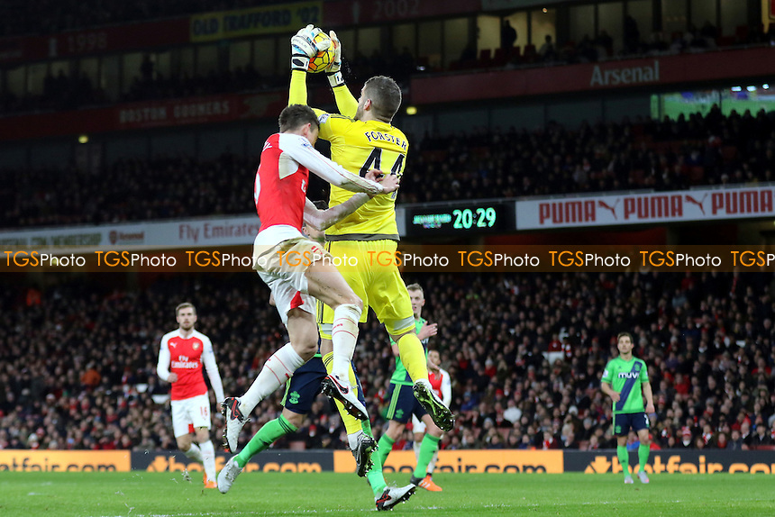 Southampton goalkeeper, Fraser Forster, makes a fine save in spite of the presence of Arsenal's Laurent Koscielny during Arsenal vs Southampton, Barclays Premier League Football at the Emirates Stadium