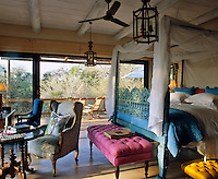 In a traditional colonial style country hotel in Africa a wall of sliding glass doors opens onto a secluded balcony