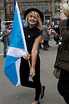 A young woman with a Scottish saltire flag at a pro-independence gathering in George Square, Glasgow. The gathering brought together Yes Scotland supporters who favour Scotland leaving the union with the United Kingdom. On the 18th of September 2014, the people of Scotland voted in a referendum to decide whether the country's union with England should continue or Scotland should become an independent nation once again and leave the United Kingdom.