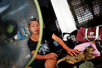 A Thai transvestite suffering from AIDS pets her cat at a hospice for those dying of AIDS at a Buddhist temple Wat Prabat Nampu, in Lopburi on the World AIDS day December 1, 2009. Thailand has been widely praised for its work in containing the virus. This remarkable achievement came about mainly because men used condoms more, and also reduced their use of brothels.  REUTERS/Damir Sagolj (THAILAND)