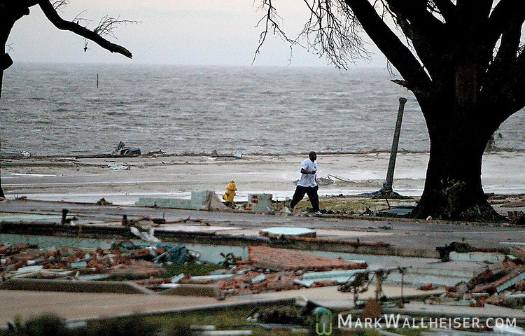A man walks through the foundations of central Biloxi beach front homes in Biloxi Mississippi a few hourse after Hurricane Katrina struck August 29, 2005.  The tropical cyclone cause catastrophic damage in Biloxi along the Mississippi Gulf coast.