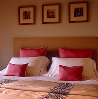 A headboard upholstered in yellow-ochre linen and plump red cushions add a feeling of warmth to the bedroom