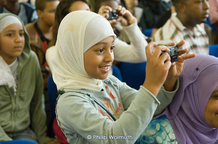 A young girl takes a photograph at a Refugee Day 2007 event at Praxis Community Projects, Bethnal Green.
