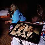 Antonia Gil, 68 - survivor, sits next to her wedding picture.