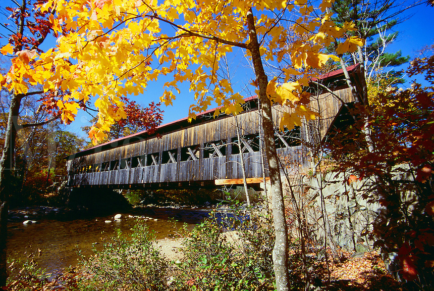 Scenic view of the White Mountain Forest Bridge on the Swift River, framed by fall foliage. New Hampshire.