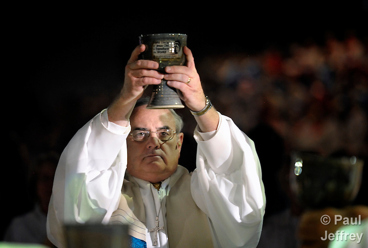 Bishop Larry M. Goodpaster lifts a chalice high during the consecration of the elements in the April 24 opening worship service of the 2012 United Methodist General Conference in Tampa, Florida.