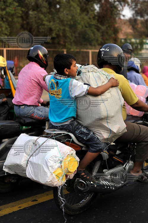 A boy rides on the back of a motorcycle on a crowded street..