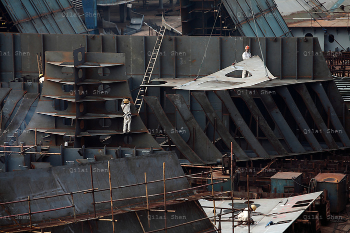 Workers operate on a ship frame at the China CSSC Holdings Ltd. Chengxi Shipyard in Jiangyin, China, on Sunday, Sept. 12, 2010. China CSSC Holdings Ltd., the nation's biggest shipyard, sees orders surge as China's voracious appetite for commodities demands more fleets of large vessels.