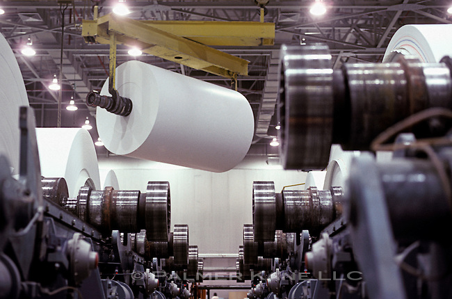 20 ton roll of coated white paper with spindle on crane hook at mill