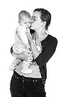Cute black and white photograph of mum kissing daughter affectionately in her arms.