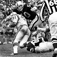 Oakland Raider linebacker Duane Benson dives on Baltimore Colt back Tom Matte..(1971 photo/Ron Riesterer)