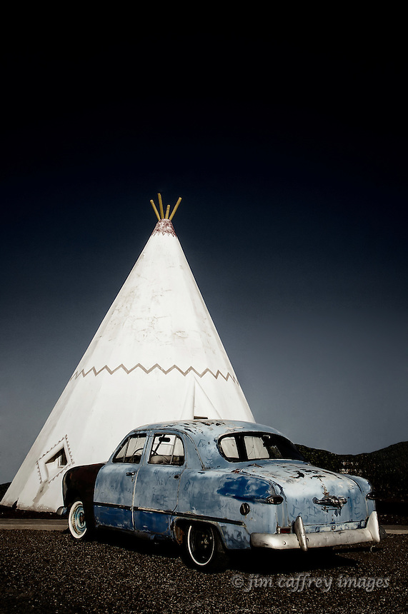 An old car parked outsite a teepee shaped motel room at the Wigwam Motel in Holbrook Arizona