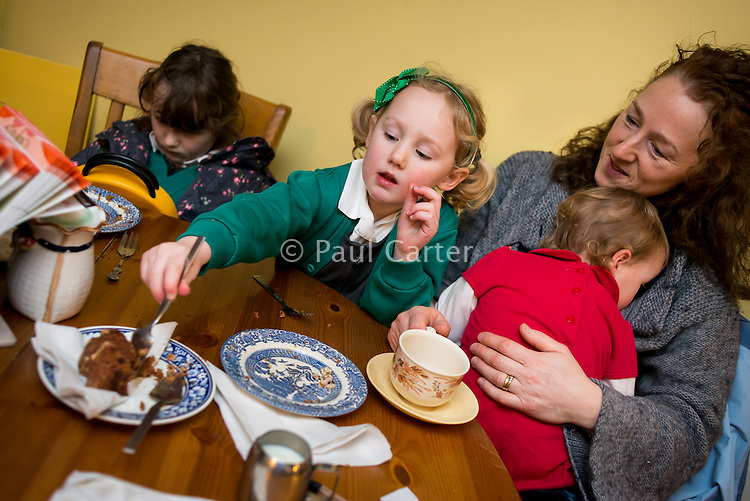 A woman breastfeeds her 20 month old toddler in a cafe, while the older sister eats cake.<br /> <br /> 07/02/2013<br /> Hampshire, England, UK