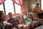 51 year old Goh Kuam Boon, a former pig farmer and a  survivor of the Nipah virus seen with his brother (right) and a friend, Thomas Wang (left) in his house in Bukit Pelandok in Nageri Sembilan, Malaysia on October 16th, 2016. <br /> In September 1998, a virus among pig farmers (associated with a high mortality rate) was first reported in the state of Perak in Malaysia. Dr. Chua investigated and discovered the virus and it was later named, Nipah Virus. The outbreak in Malaysia was controlled through the culling of &gt;1 million pigs.